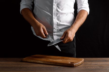 Hands of the chef closeup sharpens a kitchen knife on a knife against a dark background. The concept of cooking, cooking, recipe dishes.
