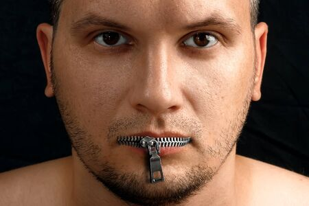 A man's mouth is closed with a zipper from his clothes. Black background. The concept of freedom of speech, closed mouth, silence problems, withholding information, pressing the media.