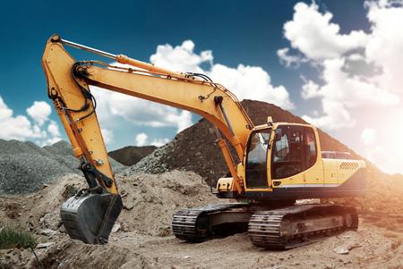 Escavatore in cantiere, sabbia, pietrisco, sullo sfondo del cielo blu. Attrezzature per l'edilizia, costruzione.