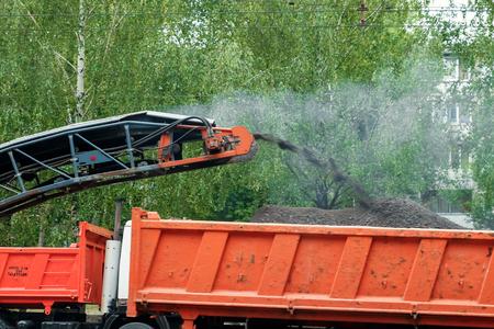 该机器正在切沥青,用特殊机切割旧沥青,并在夏日将其装入轻型罐。修理道路,替代亚福尔特,建设工作。