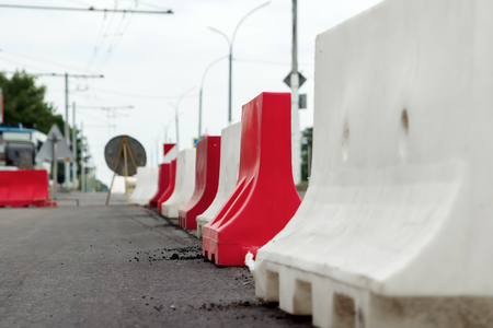 Red and white mobile plastic water filled jersey barriers for temporary limit no access work zone highway parking roadblock.