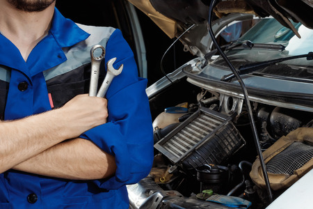 Males hands close-up with wrenches. The auto mechanic works in the garage. Repair service. Maintenance of the car, car repair.