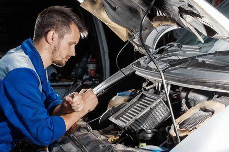 The auto mechanic works in the garage. Repair service. Maintenance of the car, car repair.