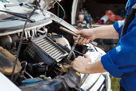 Männliche Hände Nahaufnahme mit Schraubenschlüssel. Der Automechaniker arbeitet in der Garage. Reparaturdienst. Wartung des Autos, Autoreparatur. Standard-Bild