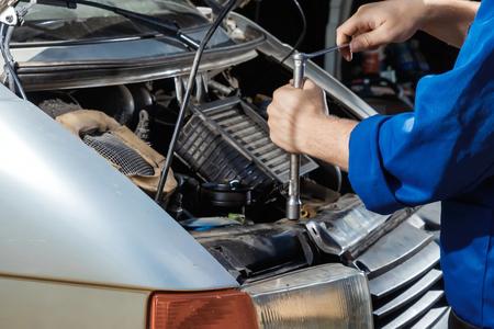 Männliche Hände Nahaufnahme mit Schraubenschlüssel. Der Automechaniker arbeitet in der Garage. Reparaturdienst. Wartung des Autos, Autoreparatur.