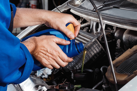 Males hands close-up pour oil into the motor. The auto mechanic works in the garage. Repair service. Maintenance of the car, car repair.
