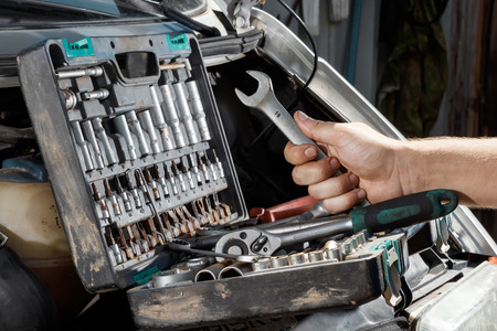 Males hand close-up with wrenches. The auto mechanic works in the garage. Repair service. Maintenance of the car, car repair. 版權商用圖片