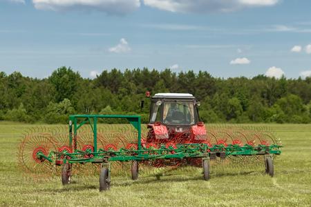 Landmaschinen, ein Traktor, der Gras auf einem Feld vor blauem Himmel sammelt. Heuernte, Grasernte. Saisonernte, Gras, landwirtschaftliche Flächen. Standard-Bild
