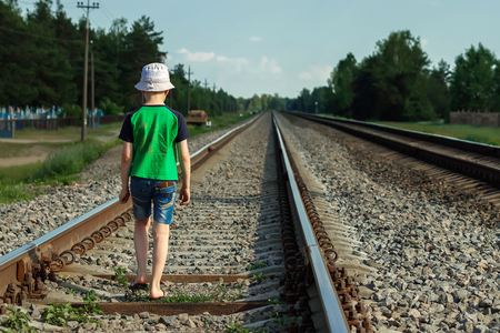 The child goes on rails, walks on rails. Danger, road, choice of profession. Banque d'images