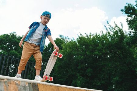 A small city boy and a skateboard. A young guy is riding in a park on a skateboard. City Style. City children. A child learns to ride a skateboard Foto de archivo