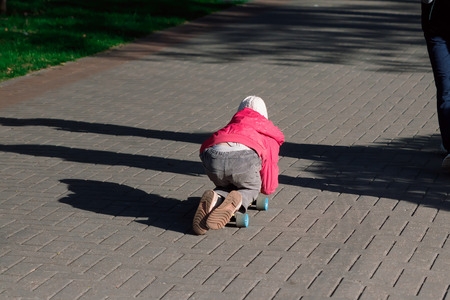 A little girl riding skateboard on city streets. Children's sports.