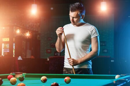 A man in a white T-shirt is playing billiards, a dark background. Pleasant pastime, entertainment, leisure, family holidays, games.