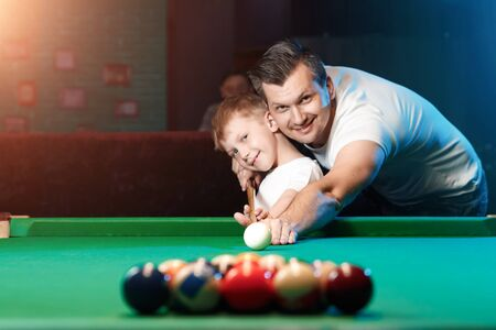 Father and son play billiards. The father teaches his son to play billiards. The concept of parents and children, upbringing, family rest.
