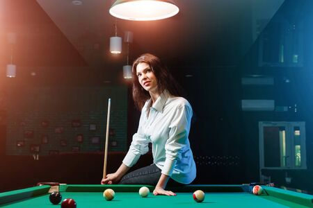 Young beautiful girl posing at a billiard table. Dark background. Pleasant pastime, rest, entertainment. Фото со стока