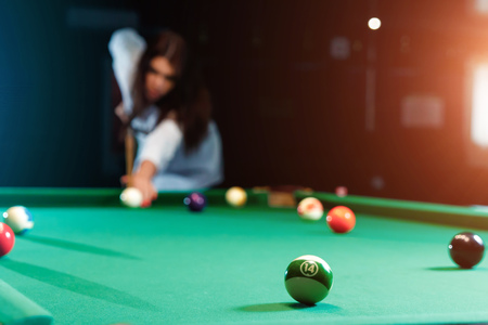 Young beautiful girl is playing billiards. Dark background. Pleasant pastime, rest, entertainment.