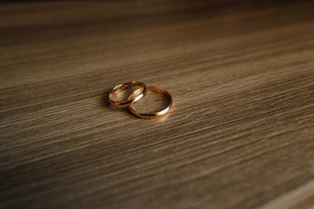 Beautiful picture with wedding rings lie on a wooden surface background.