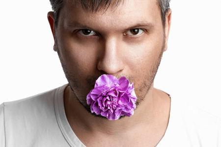 Face of a man with a purple bud of a carnation in the mouth, a flower in the mouth of a man on a white background. Close-up. The concept of tolerance, gay tolerance, the problem of gays, gay marriage. Banco de Imagens