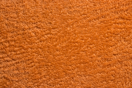 texture of an orange fabric with a long pile, close-up, top view