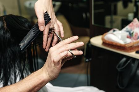 Gros plan d'un coiffeur coupant les cheveux d'une femme dans un salon de beauté