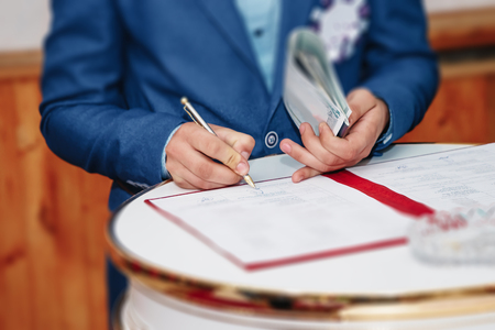 Man businessman signs documents with a pen making the signature sitting at the desk in the light. With retro effect. Imagens