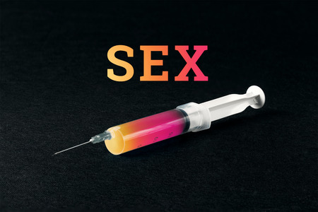 A syringe on a black background and the word sex. The concept of sex addiction, sexism.