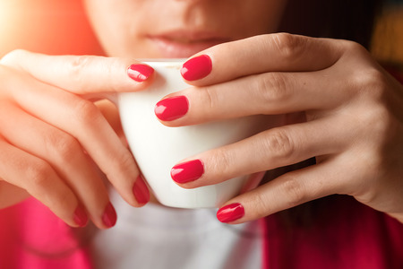 A cup of tea or coffee in the hands of a woman, pink manicure, close-up. The concept of cold weather. Reklamní fotografie - 122339747
