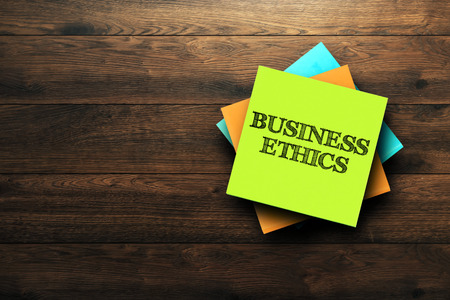 Business Ethics, the phrase is written on multi-colored stickers, on a brown wooden background. Business concept, strategy, plan, planning.