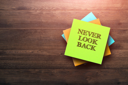 Never Look Back, the phrase is written on multi-colored stickers, on a brown wooden background. Business concept, strategy, plan, planning.
