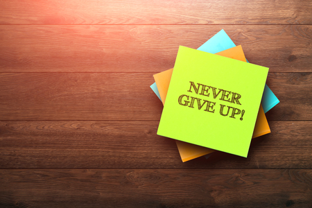 Never Give Up, the phrase is written on multi-colored stickers, on a brown wooden background. environment concept, strategy, plan, planning.