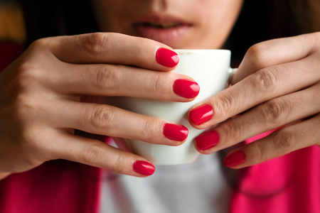 A cup of tea or coffee in the hands of a woman, pink manicure, close-up. The concept of cold weather.