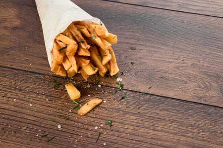 Pommes frites, in einer Papiertüte auf einem hölzernen braunen Hintergrund, Nahaufnahme.
