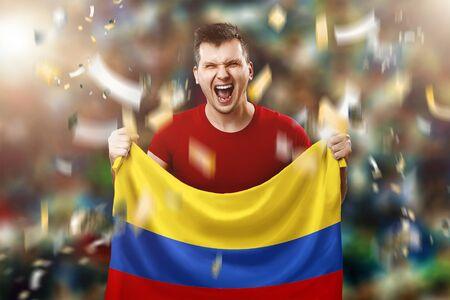 A Colombian fan, a fan of a man holding a Colombian national flag in his hands. Soccer fan in the stadium.