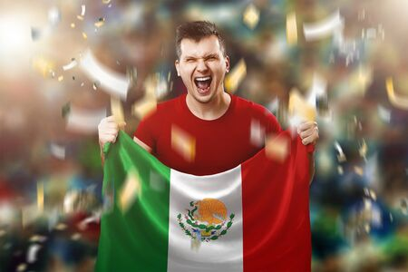 A Mexican fan, a fan of a man holding the national flag of Mexico in his hands. Soccer fan in the stadium.