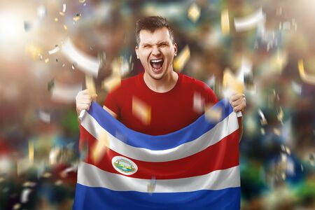 Costa Rica is a fan, a fan of a man holding the national flag of Costa Rica in his hands. Soccer fan in the stadium.