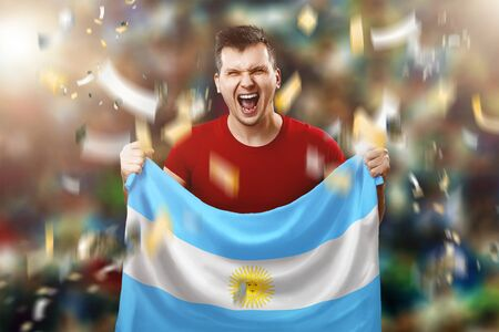 Argentine fan, fan of a man holding the national flag of Argentina in his hands. Soccer fan in the stadium. Banque d'images