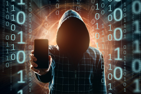 A young hacker in a hood hacks a smartphone, a hacker attack, a silhouette of a man, mixed media. The concept of a sudden attack, cryptography, data security, mobile Internet. Banco de Imagens