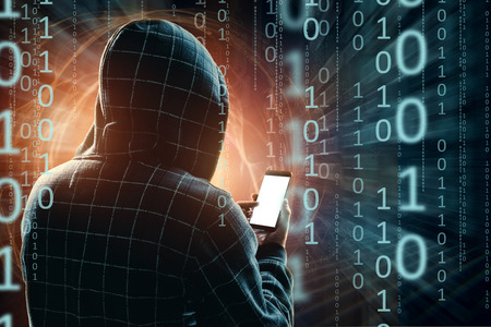 A young hacker in a hood hacks a smartphone, a hacker attack, a silhouette of a man, mixed media. The concept of a sudden attack, cryptography, data security, mobile Internet. 版權商用圖片