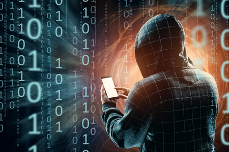 A young hacker in a hood hacks a smartphone, a hacker attack, a silhouette of a man, mixed media. The concept of a sudden attack, cryptography, data security, mobile Internet. Imagens