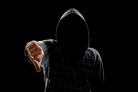 Silhouette of a man in a hood on a black background, his face is not visible, showing a fist in the camera. The concept of a criminal, incognito, mystery, secrecy, anonymity.