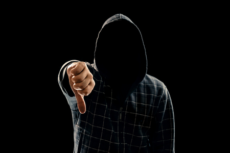 Silhouette of a man in a hood on a black background, his face is not visible, showing a fist in the camera. The concept of a criminal, incognito, mystery, secrecy, anonymity. Stock fotó