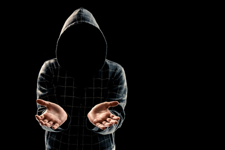 Silhouette of a man in a hood on a black background, the face is not visible, shows the palms in the camera. The concept of the criminal is given, incognito, secret, secrecy, anonymity.