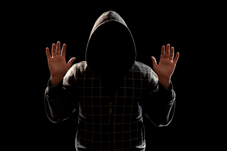 Silhouette of a man in a hood on a black background, the face is not visible, shows the palms in the camera. The concept of a criminal, incognito, mystery, secrecy, anonymity.