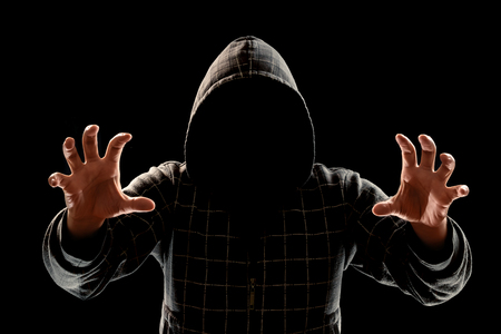 Silhouette of a man in a hood on a black background, his face is not visible, trying to attack. The concept of a criminal, incognito, mystery, secrecy, anonymity.