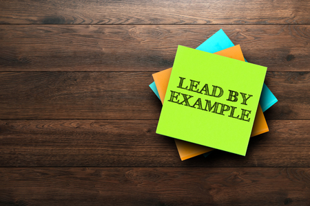 Lead by Example, the phrase is written on multi-colored stickers, on a brown wooden background. Business concept, strategy, plan, planning.