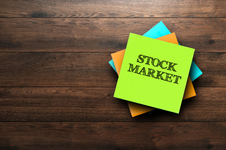 Stock Market, the phrase is written on multi-colored stickers, on a brown wooden background. Business concept, strategy, plan, planning.