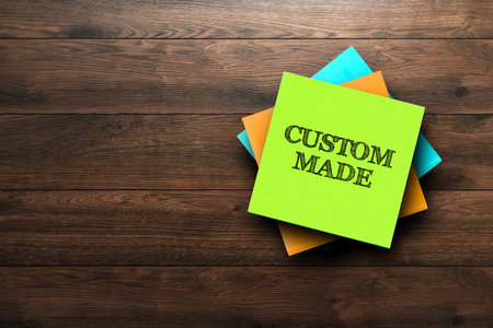 Custom Made, the phrase is written on multi-colored stickers, on a brown wooden background. Business concept, strategy, plan, planning. 免版税图像
