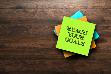 Reach Your Goals, the phrase is written on multi-colored stickers, on a brown wooden background. Business concept, strategy, plan, planning.