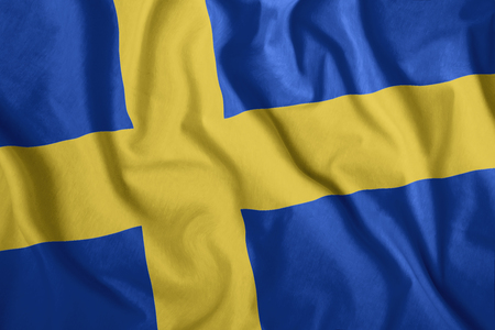 The Swedish flag is flying in the wind. Colorful national flag of Sweden. Patriotism, patriotic symbol.