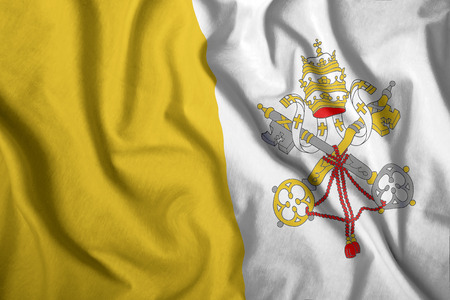The Vatican flag flies in the wind. Colorful national flag of the Vatican. Patriotism, patriotic symbol. Stock Photo