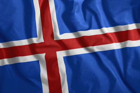 The Icelandic flag flutters in the wind. Colorful, national flag of Iceland. Patriotism, a patriotic symbol.